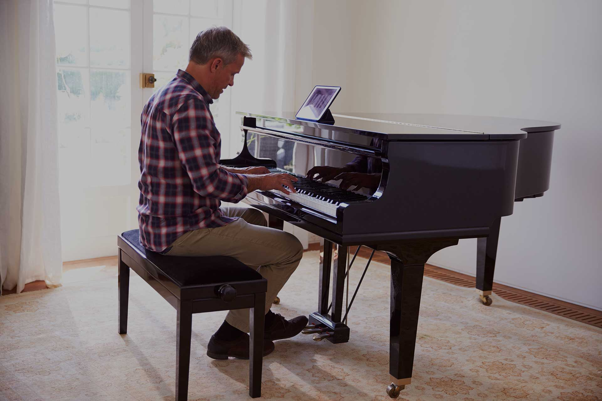 Man learning the piano via a tablet