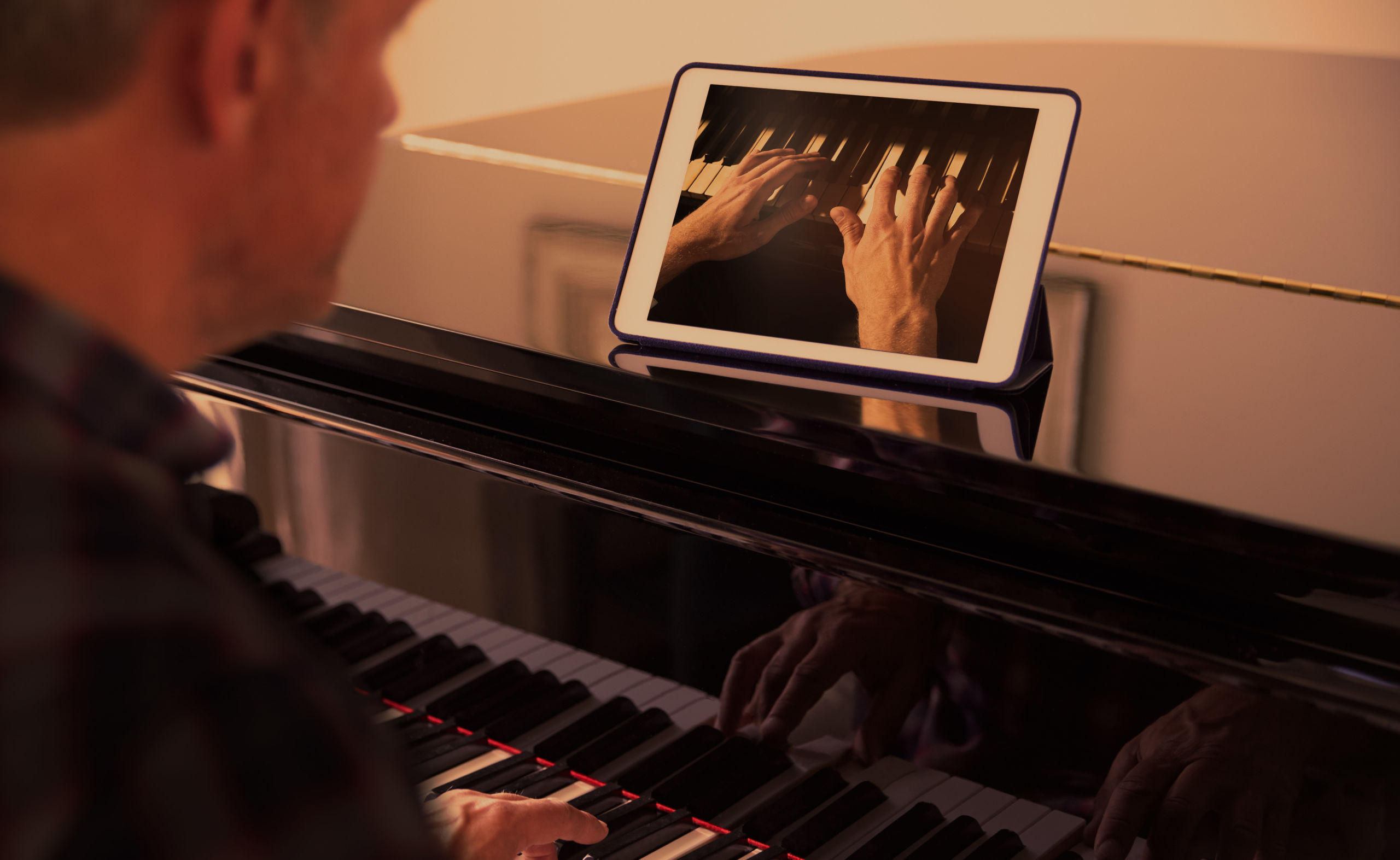Man with tablet on the piano
