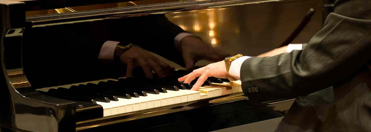 man playing on a grand piano
