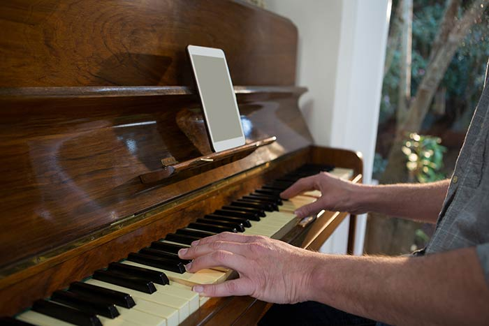 man playing the piano with ipad feat