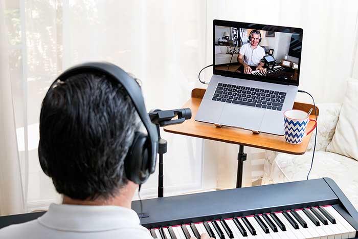 man teaching piano online feat
