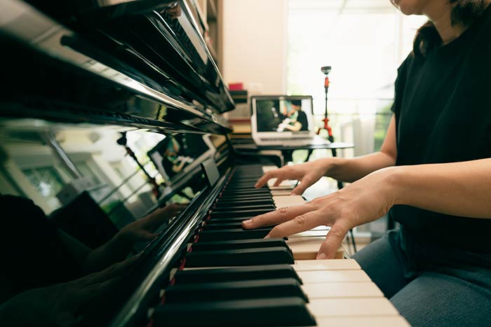 woman having online piano lessons feat