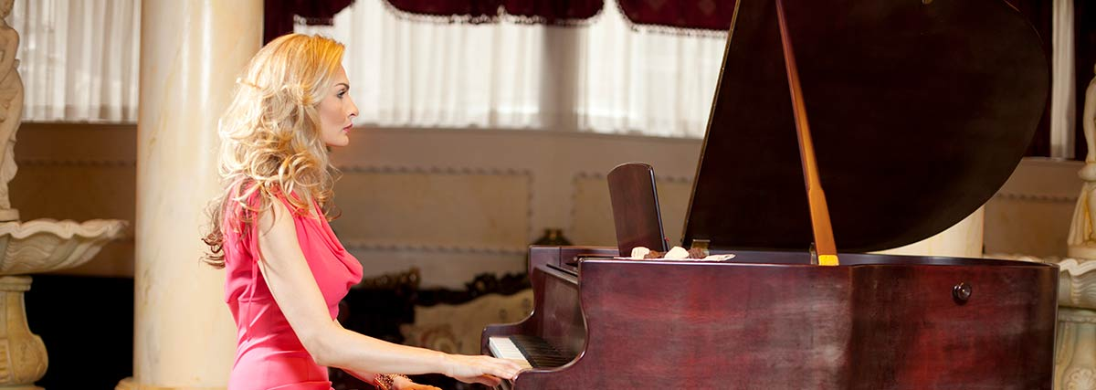 woman in pink dress playing the piano