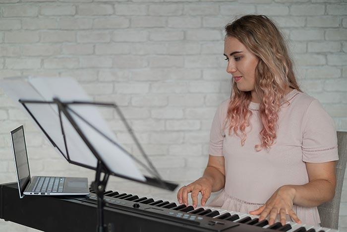 woman teaching piano online feat